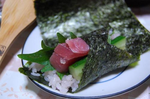 海苔に寿司飯、キュウリ、青ジソ、マグロを乗せて巻く
